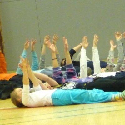 Lapsia makaa koulusalin lattialla kädet ylhäällä.