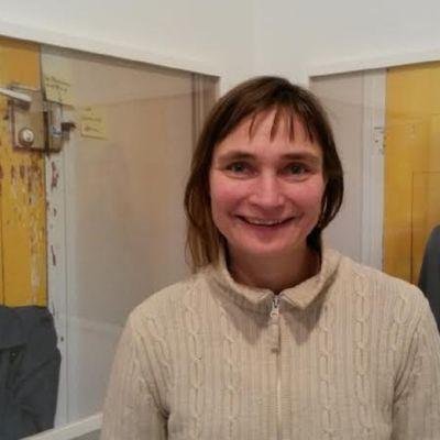 kvinna mellan två fotoverk med en gul dörr i bakgrunden och en kvinna framför dörren