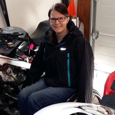 Nuori nainen istuu pyörätuolissa moottoripyöriennsä keskellä.