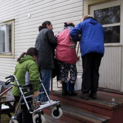 Kolme ihmistä auttaa  vanhusta portaita ylös.