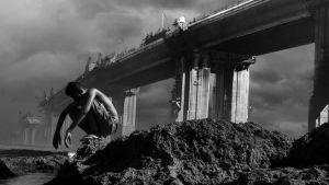 mustavalkoinen valokuva fiktiivisen lyhytelokuvan päähenkilöstä kyykyssä sillan alla.