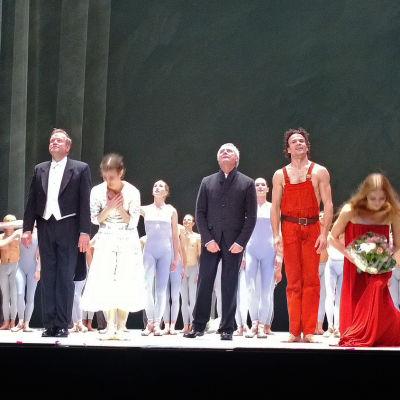 Peer Gynt -baletin loppukiitoksissa frakkipukuinen Markus Lehtinen, sekä myös koreografi John Neumeier, jonka vieressä seisoo oranssihaalarinen Peer Gynt eli Carsten Jung.