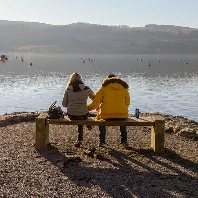 Pariskunta istuu penkillä veden äärellä.