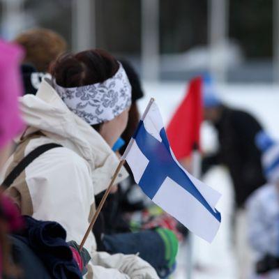 Suomen lippu heiluu katsomossa.