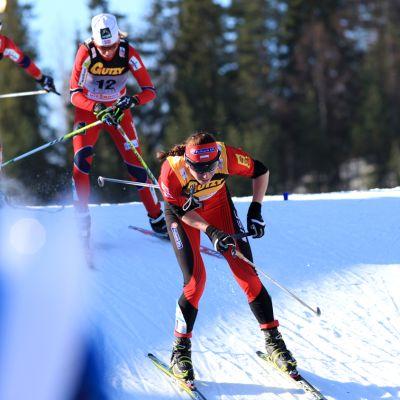 Hiihtäjät kirittävät toisiaan naisten skiathlonissa.