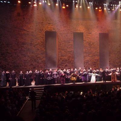 Kaikki oopperan esiintyjät lavalla vastaanottamassa suosionosoituksia Savonlinnan Oopperajuhlilla.