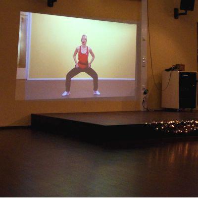 Virtuaalijumppatunnin vetäjä katsoo salin seinältä