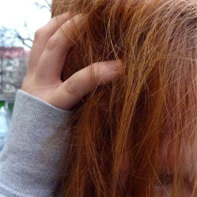 Nainen haroo kädellään sähköisiä hiuksiaan.