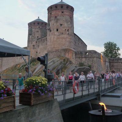 Ihmisiä kävelee Olavinlinnan sillalla pois linnasta, Olavinlinna näkyy taustalla.