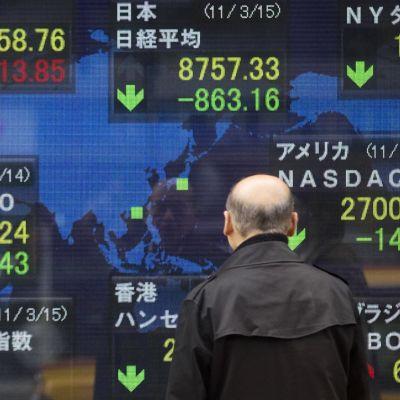 Ihmiset seuraavat näyttötaululta pörssikurssien syöksymistä: