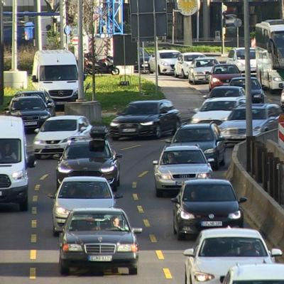 Många bilar kör efter varandra på en gata.