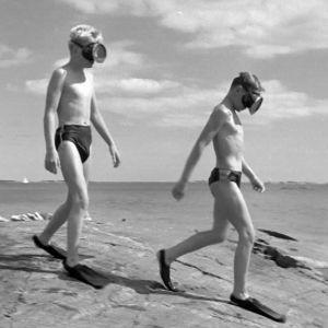 Pojat sukellusvarusteissa rannalla