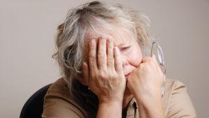 närbild på äldre kvinna som ser trött ut