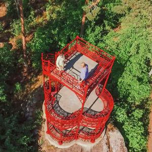 Ylhäältä kuvattu punainen näköalatorni kalliolla, tornissa kaksi ihmistä.