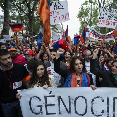 Ihmisjoukko lippujen ja kylttien kanssa, kyltissä lukee kansanmurha