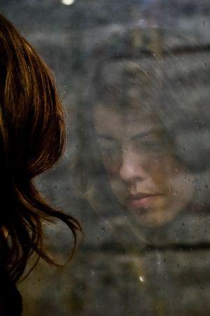 Naisen kasvot heijastuvat tummasta ikkunasta