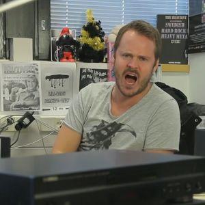 Dan sitter vid skrivbordet och skriker mot kameran