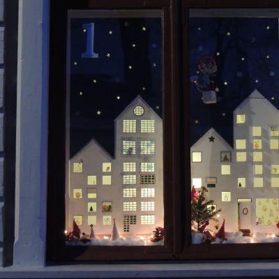 kaupungin silhuetti ja tonttuja ikkunassa
