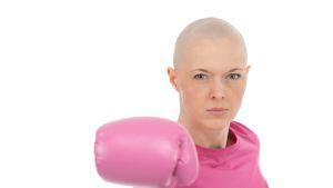 en kvinna med bröstcancer som har rosa kläder och rosa boxningshandskar på sig