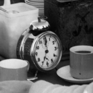 Herätyskello ja kahvikuppi toripöydällä