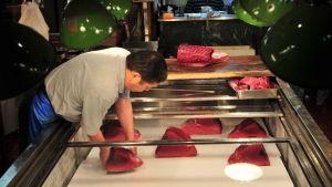 Japansk man lägger om fiskbitar på Tokyos fiskmarknad