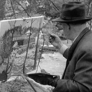 Mies maalaa keväistä maisemaa.