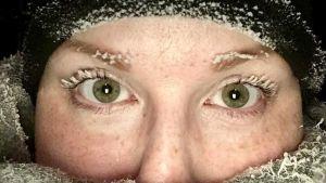 Lähikuvs naisen kasvoista, jonka ripset ovat jäätyneet pakkasessa