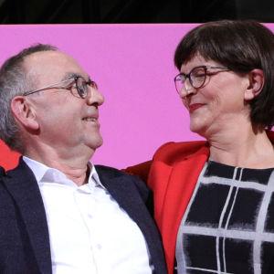 Norbert Walter-Borjans och Saskia Esken tittar på varandra och ler, Esken har sin arm runt Walter-Borjans.
