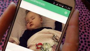 Älypuhelimen näytöllä nukkuva vauva