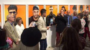 Vernissage av en fotoutställning. Färggranna foton hänger på väggen. Två fotografer i förgrunden, den ena fotar den andra med sin telefon. Publik syns nere på bilden.