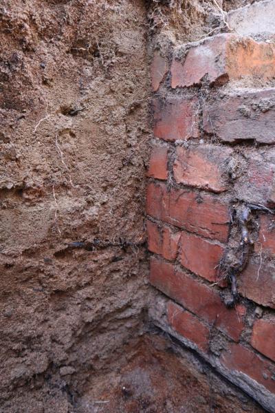 en röd tegelvägg som grävts fram under jorden. I de röda teglen finns rester av rötter och sand som ätit sig in i murbruket.