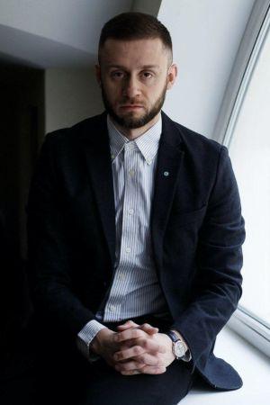 Epidemiologen Anton Bartjuk sitter på ett fönsterbräde med knäppta händer och ser in i kameran.
