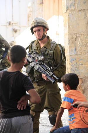 Israelisk soldat står vakt kring bosättare i Hebron