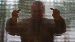 Man visar mittenfinger bakom en glasvägg.