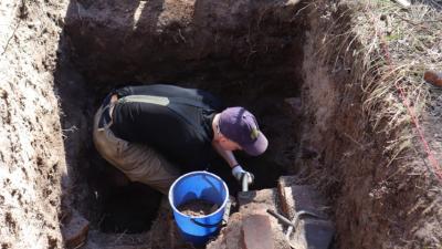 En man står nerböjd en bra bit under jord och gräver försiktigt. Man kan se trappsteg som leder till något som finns långt under markytan.