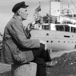 Mies istuu satamassa
