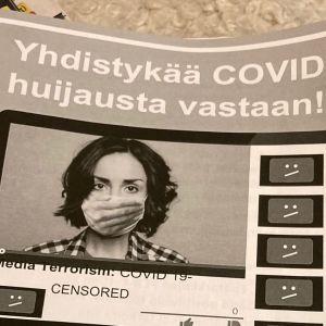 Närbild på en broschyr där det påstås att en konspiration ligger bakom coronaviruset.