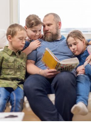 Aleksei Roganov sohvalla kolmen lapsensa kanssa.