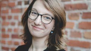 Maija Pelli står i svart blus framför brun tegelvägg.
