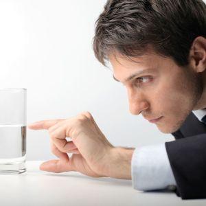 En man tittat på ett halvtomt, eller halvfullt glas.