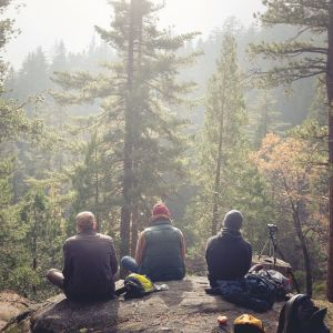 Kolme miestä patikoimassa