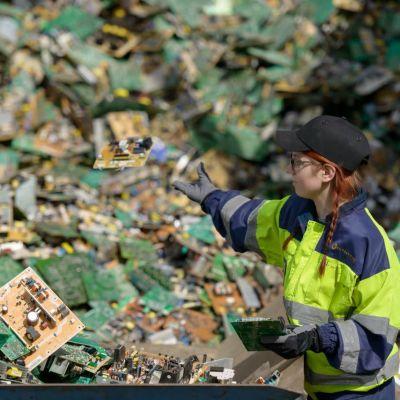 Kuusankoski Oy:n työntekijä heittää elektroniikkajätettä jätekasaan.