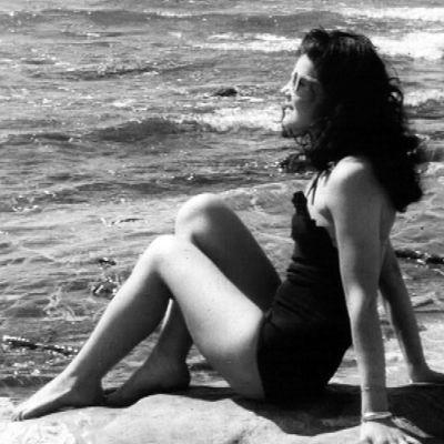 Nainen ottaa aurinkoa rannalla.