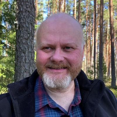 Mies taustallaan metsä.