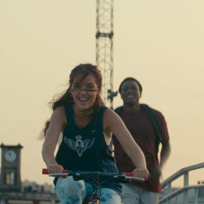 En flicka cyklar och en pojke springer bakom henne med blicken riktad mot kameran.