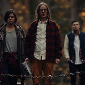 Tre ungdomar står mitt i en mörk skog och blickar mot sin kommande övernattningsplats.