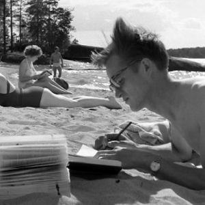 Mies lukee kirjaa rannalla.