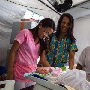 En baby sköts av tre kvinnor