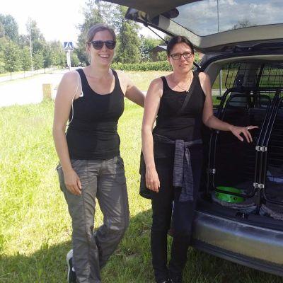 Kuvassa kaksi naista auton takakontin edessä.