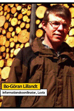 Bo-Göran Lillandt i brun jacka står framför en stor vedhög som en vägg av stockar.